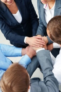 Image of business people keeping their hands in pile symbolizing support and power
